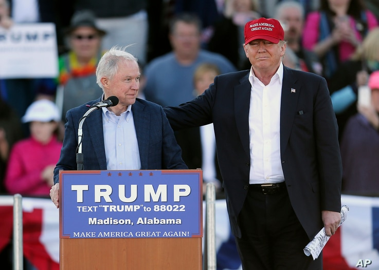 FILE - Then-Republican presidential candidate Donald Trump stands next to Sen. Jeff Sessions, R-Ala., as Sessions speaks during a rally in Madison, Ala., Feb. 28, 2016.
