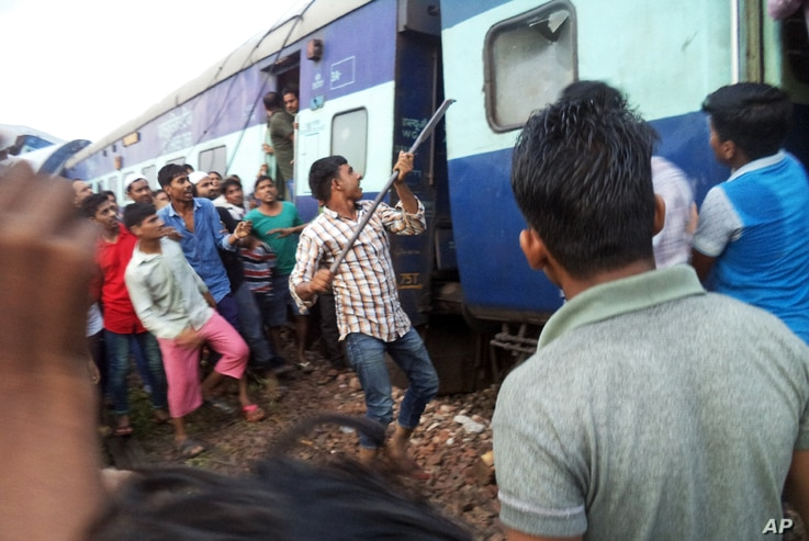 A volunteer breaks the glass of a train compartment window to rescue passengers trapped after an accident near Khatauli, in the northern Indian state of Uttar Pradesh, Aug. 19, 2017.