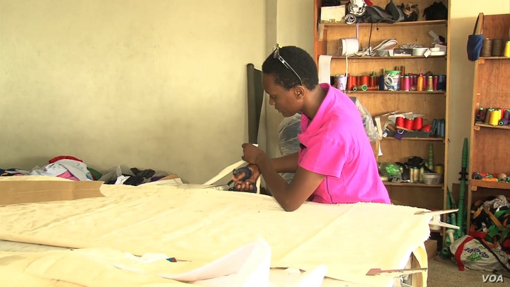 Lilian Wairimu cuts the material needed for the beanbag. The material is cut into eight pieces with inner and outer lining, then is stitched together with a zipper to hold the foam perfectly. (M. Yusuf/VOA)