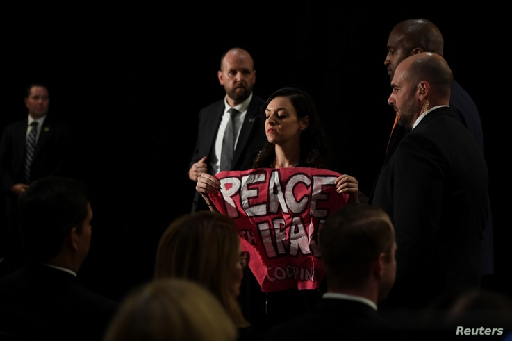 """A protester holding a sign that says """"Peace with Iran"""" is escorted out of the room during U.S. Secretary of State Mike Pompeo's remarks during the United Against Nuclear Iran Summit on the sidelines of the U.N. General Assembly in New York, Sept. 25,..."""