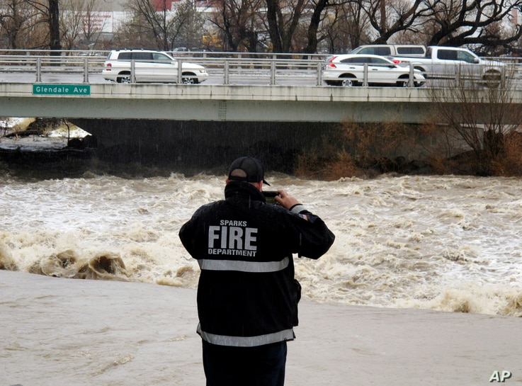 A Sparks firefighter takes a picture of the rising Truckee River, Sunday, Jan. 8, 2017, where it runs near the Grand Sierra hotel-casino along a line that divides the cities of Reno and Sparks, Nevada.