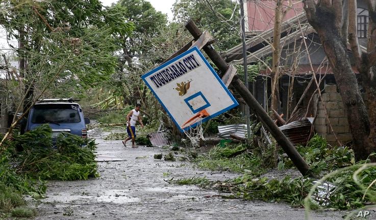 A resident walks beside a toppled basketball court after Typhoon Mangkhut barreled across Tuguegarao city,  Cagayan province, northeastern Philippines, Sept. 15, 2018.