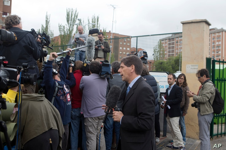 A U.S. TV journalist reports from outside the Carlos III Hospital in Madrid, Spain, Tuesday, Oct. 7, 2014. Spanish and foreign media are camped outside the hospital while Spain placed in quarantine the husband of a Spanish nurse who has tested positi...
