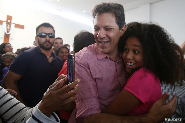A woman takes a photo with Fernando Haddad, presidential candidate of Brazil's leftist Workers' Party   after a celebration mass in Sao Paulo, Brazil, Oct. 12, 2018.