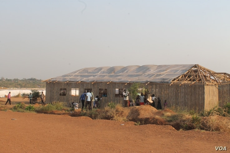 South Sudanese bustle about outside the 14-square-meter structure that has been covered with plastic sheeting and turned into a place of worship in the U.N. House IDP camp in Juba, in the days before Christmas 2014..