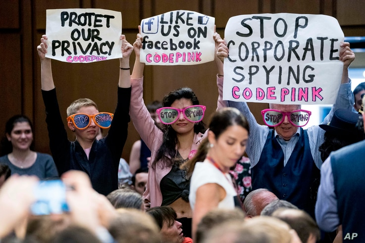 """Members of the audience hold up signs and wear sunglasses that read """"Stop Spying"""" before CEO Mark Zuckerberg arrives to testify before a joint hearing of two Senate committees on Capitol Hill in Washington, April 10, 2018, about the use of Facebook d..."""