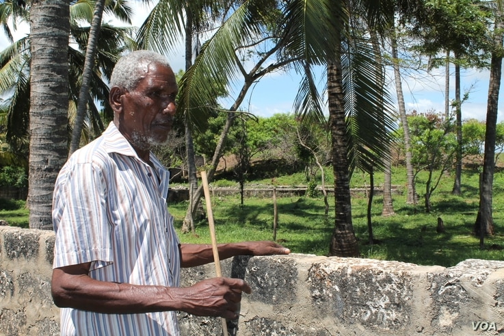 Piry Muye stands beside a stone wall fencing off the land that was once his, Mombasa, Kenya, November 18, 2012. (H. Heuler/VOA)