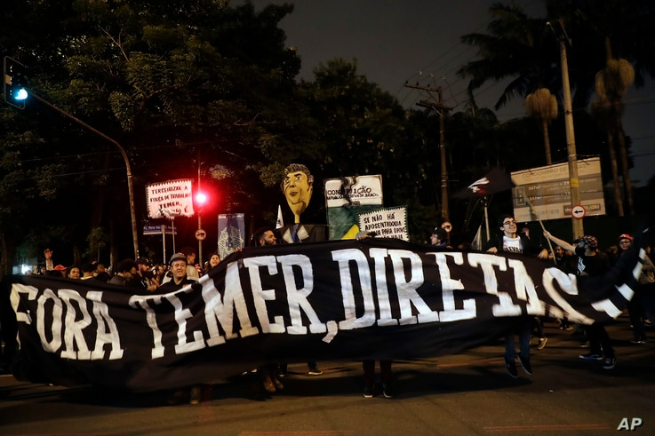 "Demonstrators protest holding a banner that reads in Portuguese ""Get out Temer, elections now,"" outside the residence of Brazil's President Michel Temer during a general strike in Sao Paulo, Brazil, April 28, 2017. Buses, trains and metros have been ..."