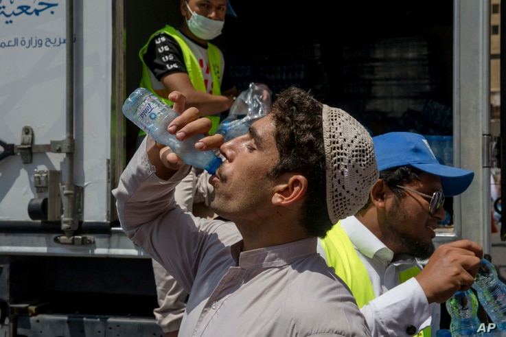 A Muslim pilgrim drinks water distributed by Saudi volunteers near the Grand Mosque, ahead of the annual Hajj pilgrimage, in the Muslim holy city of Mecca, Saudi Arabia, Aug. 18, 2018.