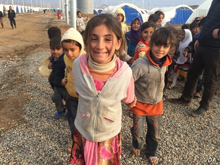 Little girls here in Khazir Camp, Kurdish Iraq say they like to pretend camp workers are giving them papers to get supplies like food and fuel on Dec. 1, 2016. (H.Murdock/VOA)