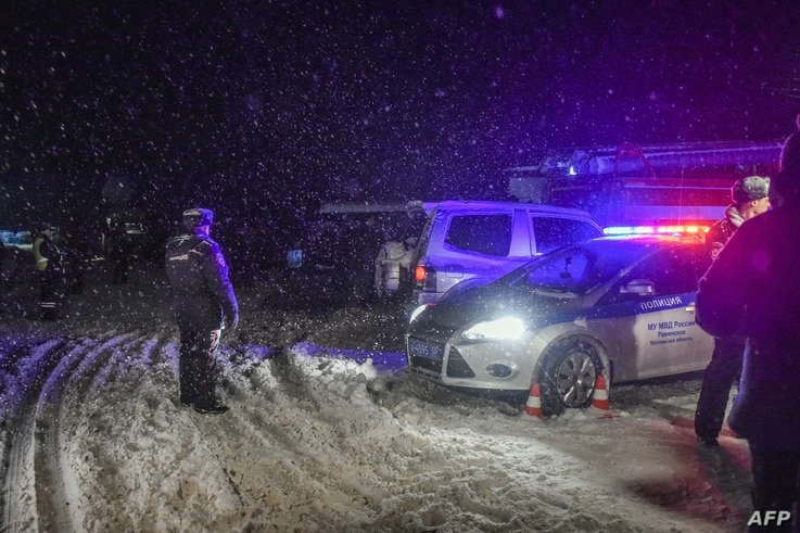 Police block the road near the site of air crash outside Moscow, Feb. 11, 2018.