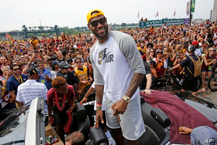 Cleveland superstar LeBron James, center, stands in the back of a Rolls Royce at the beginning of a parade in downtown Cleveland, Wedensday, June 22, 2016, celebrating the Cavaliers' NBA Championship.