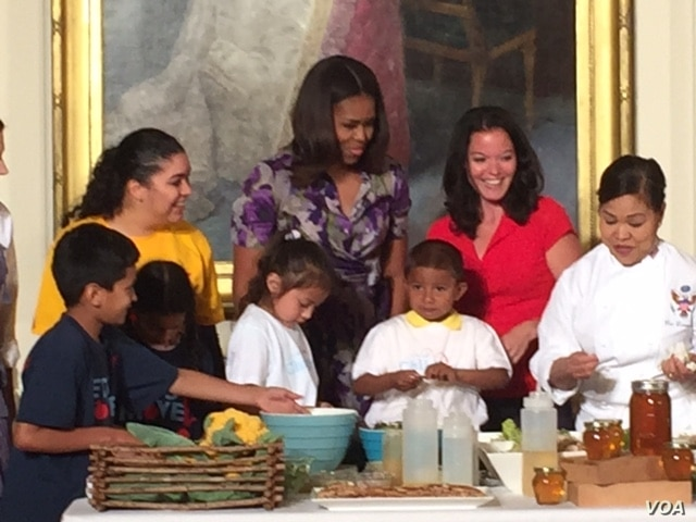"Michelle Obama, center, and Deb Eschmeyer, second from right, head of ""Let's Move!"" program, join kids in making salads from products out of the garden planted on the South Lawn of the White House earlier this year, June 3, 2015.er this year."