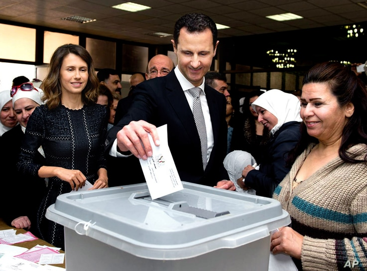 This photo released on the official Facebook page of Syrian Presidency, shows Syrian President Bashar Assad casting his ballot in the parliamentary elections, as his wife Asma, left, is standing next to him, in Damascus, Syria, Wednesday, April 13, 2...