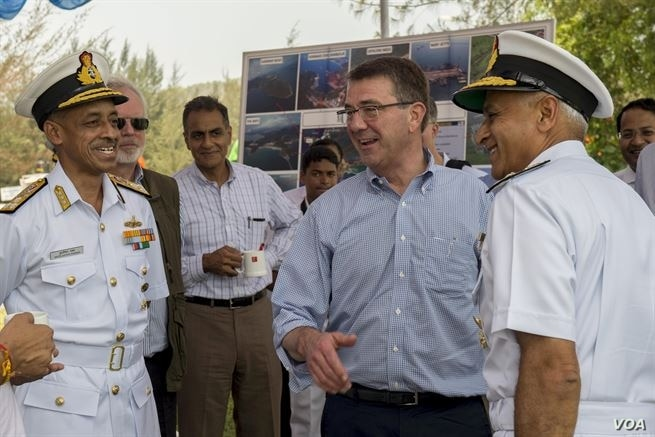 U.S. Defense Secretary Ash Carter, center right, laughs with Indian naval officers as he arrives at the Karwar naval base in India to visit the Indian aircraft carrier INS Vikramaditya, April 11, 2016.