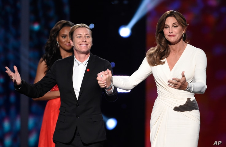 Soccer player Abby Wambach, of the U.S. women's national soccer team, left, presents Caitlyn Jenner with the Arthur Ashe award for courage at the ESPY Awards at the Microsoft Theater in Los Angeles, July 15, 2015.