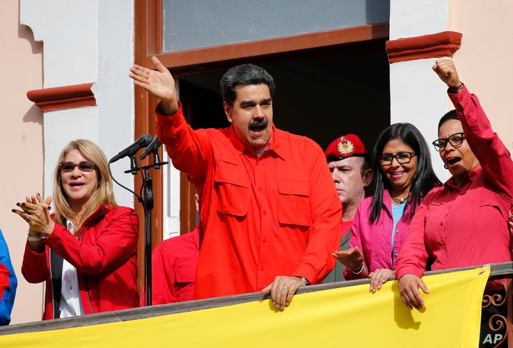 Venezuela's President Nicolas Maduro, center, and first lady Cilia Flores, left, interact with supporters from a balcony at Miraflores presidential palace during a rally in Caracas, Venezuela, Jan. 23, 2019.