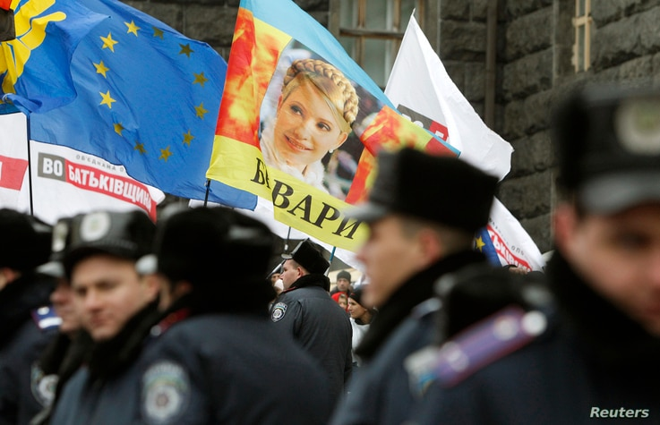 A portrait of jailed opposition leader Yulia Tymoshenko is seen on a flag during a rally to support EU integration in Kyiv, Nov. 26, 2013.