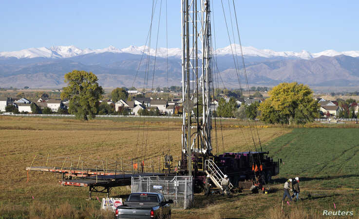 Workers drill an oil well within sight of houses against a Rocky Mountain backdrop near Longmont, Colorado, Oct. 14, 2014.