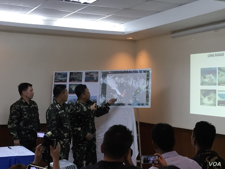 Philippine Armed Forces Chief of Staff General Gregorio Pio Catapang uses a laser pointer to show reclamation work on a reef the Philippines claims, Armed Forces General Headquarters, Quezon City, Philippines, April 20, 2015.  (Simone Orendain/VOA)