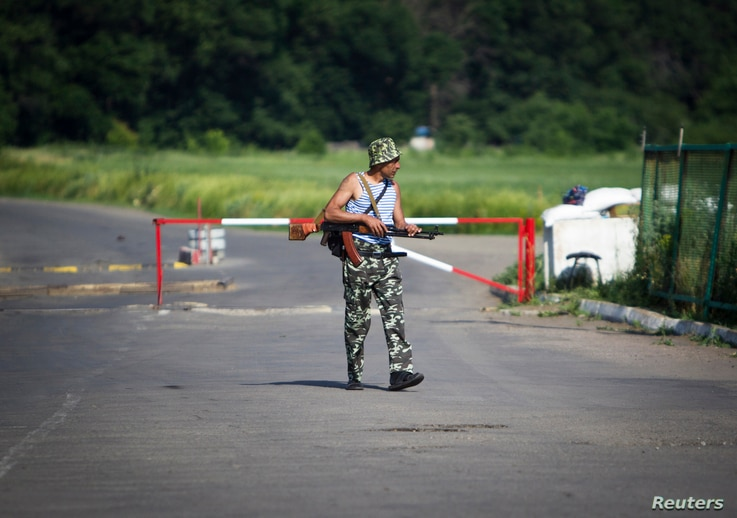 An armed pro-Russian separatist guards a border post abandoned by Ukrainian border guards at Chervonopartyzansk along the Ukraine-Russia border, June 7 2014.