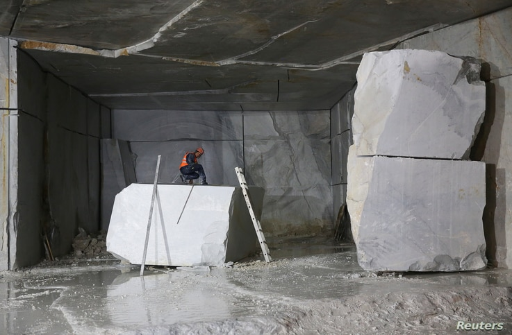 A worker measures a marble stone at the Cervaiole quarry on Monte Altissimo, Tuscany, Italy, July 14, 2017.