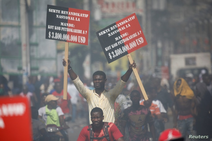 A protester holding placards rides on a motorbike during a march to demand an investigation into what they say is the alleged misuse of Venezuela-sponsored PetroCaribe funds, in Port-au-Prince, Haiti, Oct. 17, 2018.