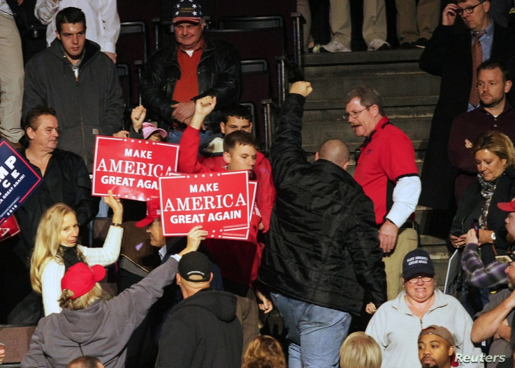 """A protester walks out at from a rally that is part of President-elect Donald Trump's and Vice President-elect Mike Pence's """"USA Thank You Tour 2016"""" in Cincinnati, Ohio, Dec. 1, 2016."""
