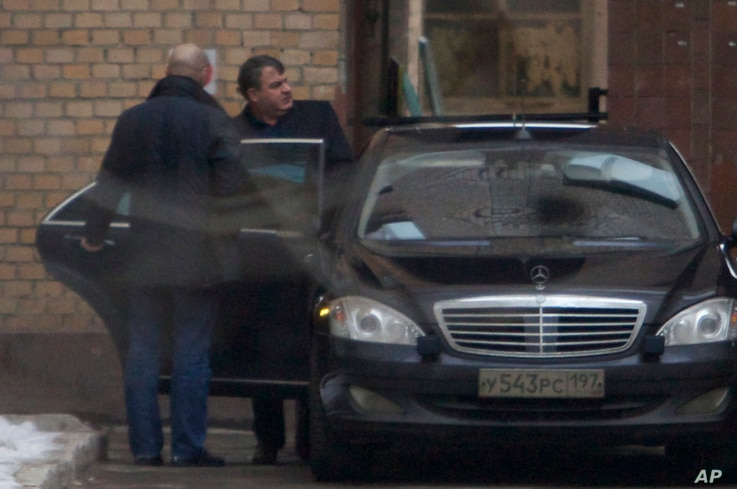 FILE - Former Russian defense minister Anatoly Serdyukov (R) is seen getting into a car in Moscow, Russia, Dec. 6, 2013. Spanish prosecuters suspect Serdyukov of having ties to the criminal underworld.