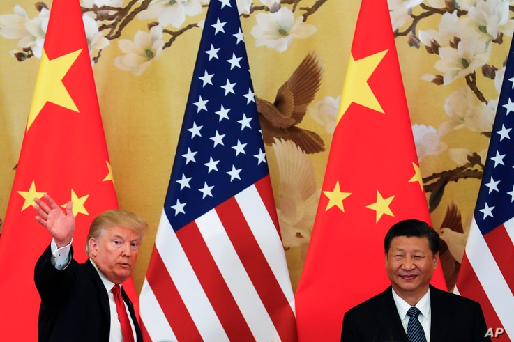 FILE - U.S. President Donald Trump waves next to Chinese President Xi Jinping after attending a joint press conference at the Great Hall of the People in Beijing.
