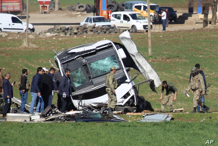 Members of Turkish forces gather around a bus that was destroyed in an explosion on the road linking the cities of Diyarbakir and Bingol, in southeastern Turkey, Feb. 18, 2016. Six soldiers were killed after PKK rebels detonated a bomb on the road.