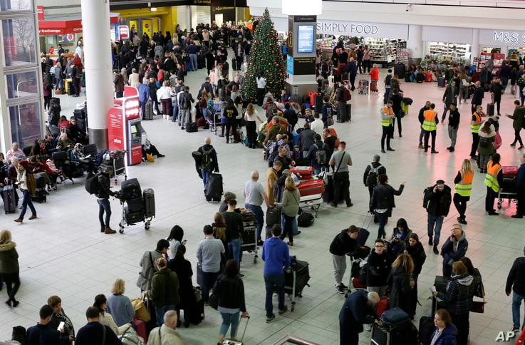 People queue at Gatwick airport, near London, as the airport remains closed with incoming flights delayed or diverted to other airports, after drones were spotted over the airfield last night and this morning, Dec. 20, 2018.