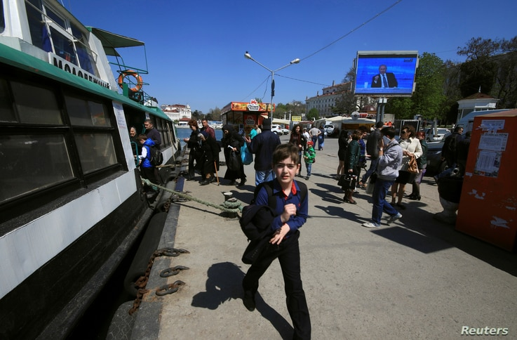 People walk under an electronic screen showing nationwide call-in attended by Russian President Vladimir Putin on a street of the Black Sea port of Sevastopol, Crimea, April 14, 2016.