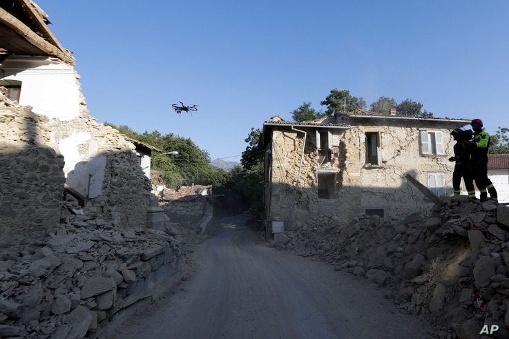 Firefighters operate a drone to survey quake-damaged buildings in the village of Cossito, central Italy, Aug. 27, 2016.