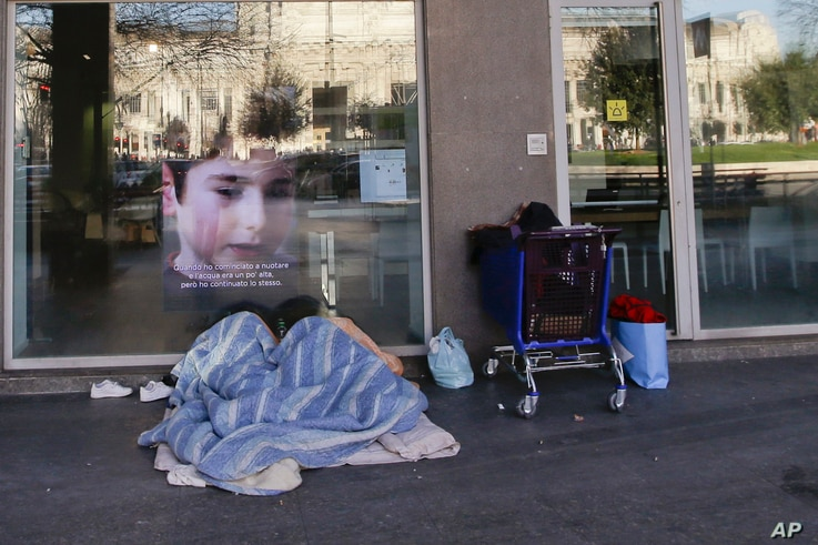 A homeless sleeps under blankets in front of the entrance of a bank, in Milan, Italy, Jan. 7, 2017. In Italy, sub-freezing temperatures were blamed on the deaths of a half-dozen homeless people, while heavy snows and high winds resulted in re-routed ...