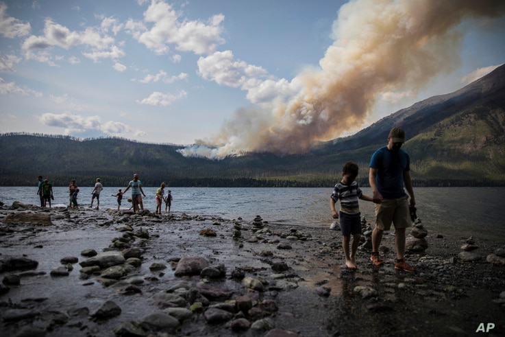 In this Aug. 12, 2018 photo provided by the National Park Service, people walk along the shore near Lake McDonald Lodge as the Howe Ridge Fire burns in Glacier National Park, Montana.