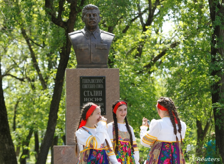 Girls react during the unveiling of a bust of Soviet dictator Joseph Stalin in the village of Trunovskoye in Stavropol region, Russia, May 5, 2017.