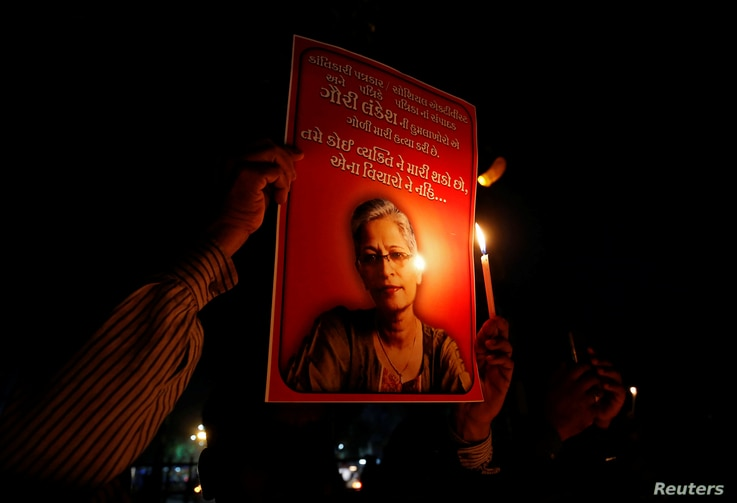 FILE - People hold placards and candles Sept. 6, 2017, during a vigil for Gauri Lankesh, a senior Indian journalist shot dead outside her home by unidentified assailants in southern city of Bengaluru, in Ahmedabad, India.
