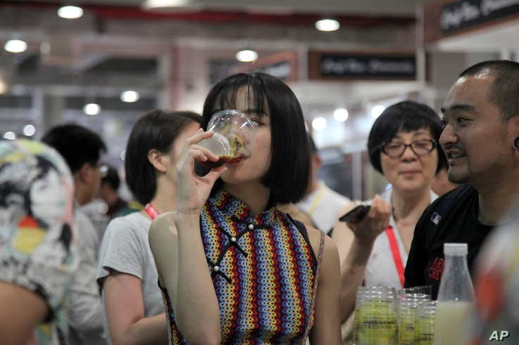 A woman drinks beer at the 2018 Craft Beer of China Exhibition in Shanghai, May 17, 2018.