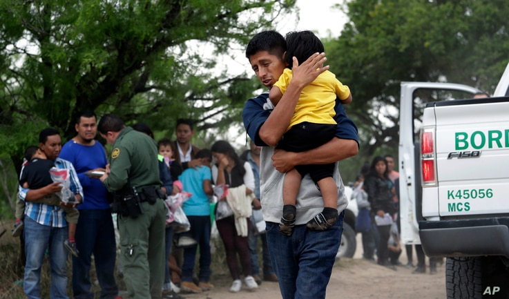 FILE - Jose Fermin Gonzalez Cruz holds his son, William Josue Gonzales Garcia, 2, as they wait with other families who crossed the nearby U.S.-Mexico border near McAllen, Texas, for Border Patrol agents to check names and documents, March 14, 2019.