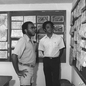 Warren Washington and a fellow student looking at weather maps in 1977.
