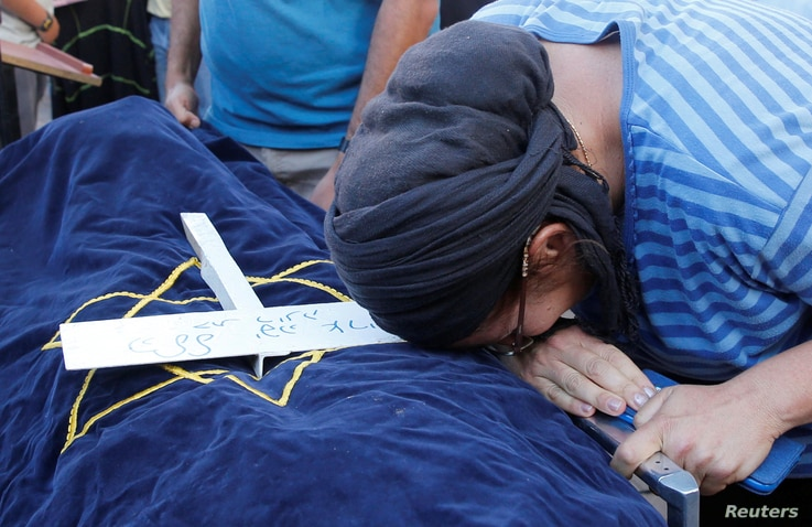 The mother of Israeli girl, Hallel Yaffa Ariel, 13, who was killed in a Palestinian stabbing attack in her home in the West Bank Jewish settlement of Kiryat Arba, mourns during her daughter's funeral at a cemetery in the West Bank city of Hebron. Jun...
