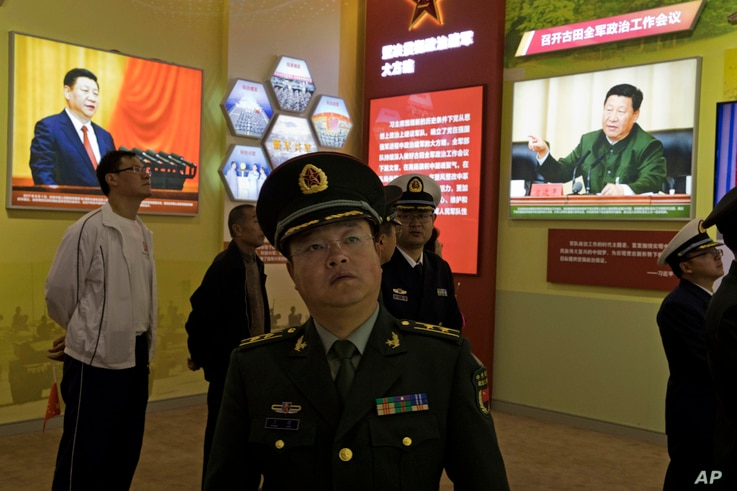 A Chinese military officer walks past photos of Chinese President Xi Jinping at an exhibition highlighting China's achievements under five years of Xi's leadership at the Beijing Exhibition Hall in Beijing, China, Oct. 17, 2017.