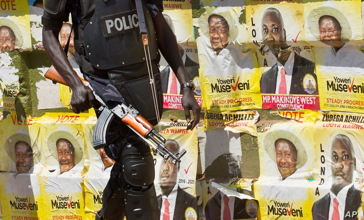 An armed Ugandan riot policeman patrols past campaign posters for long-time President Yoweri Museveni, as well as local members of Parliament, on a street in Kampala, Uganda, Feb. 17, 2016.