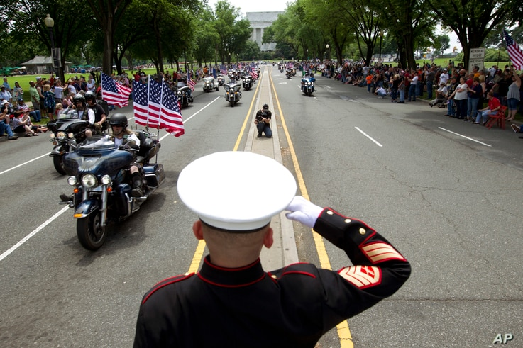 U.S. Marine Tim Chambers salutes to participants in the Rolling Thunder motorcycle rally ahead of Memorial Day on May 27, 2018, in Washington.