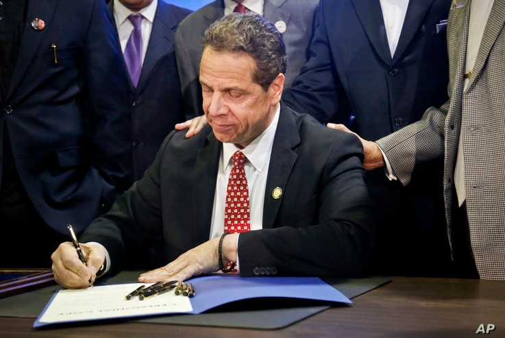 New York Gov. Andrew Cuomo signs new legislation for free state college tuition and juvenile justice reform during a signing ceremony in New York, April 10, 2017.