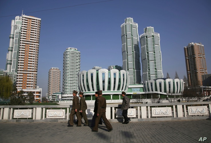 North Koreans walk past Ryomyong Street, the newest residential development in Pyongyang, North Korea, April 11, 2017. North Korean Premier Pak Pong Ju told the Supreme People's Assembly that a priority for the Cabinet this year would be improving th...
