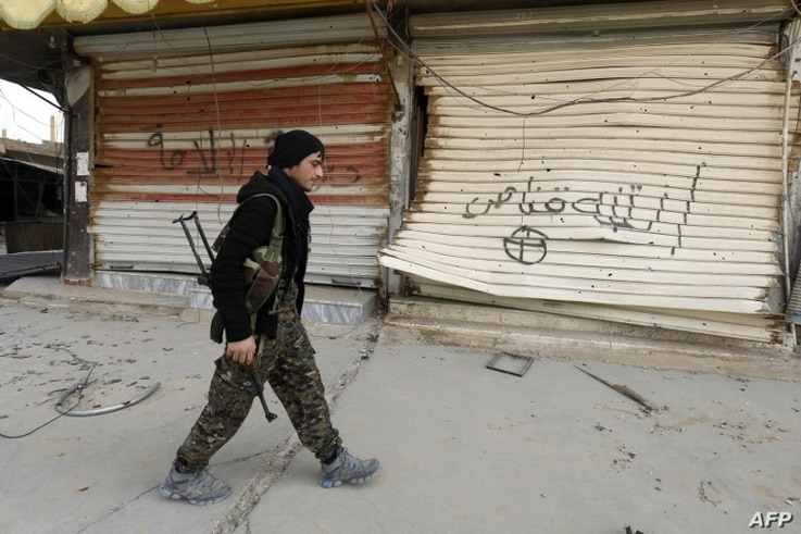 "A fighter from the Syrian Democratic Forces (SDF) walks past shops with their fronts painted with the Arabic phrases ""beware a sniper"" and ""caliphate state"", in the city of Hajin in Syria's eastern Deir Ezzor province, Jan. 27, 2019."