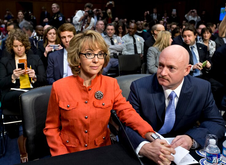 FILE - Former U.S. Rep. Gabrielle Giffords, who survived a gunshot to the head in 2011 during a mass shooting in Tucson, Ariz., sits with her husband, retired astronaut Mark Kelly, at a Senate panel hearing on gun violence, on Capitol Hill in Washing...
