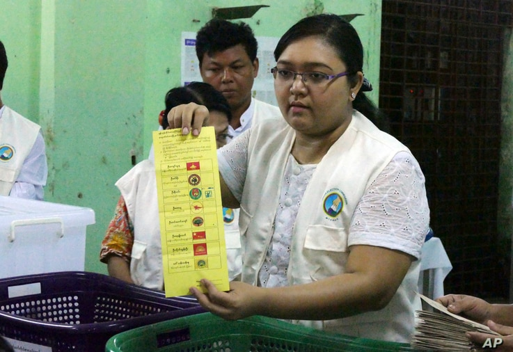 Myanmar election commission officer shows a ballot to count votes at a polling station during the country's general election, Nov. 8, 2015, in Yangon, Myanmar.